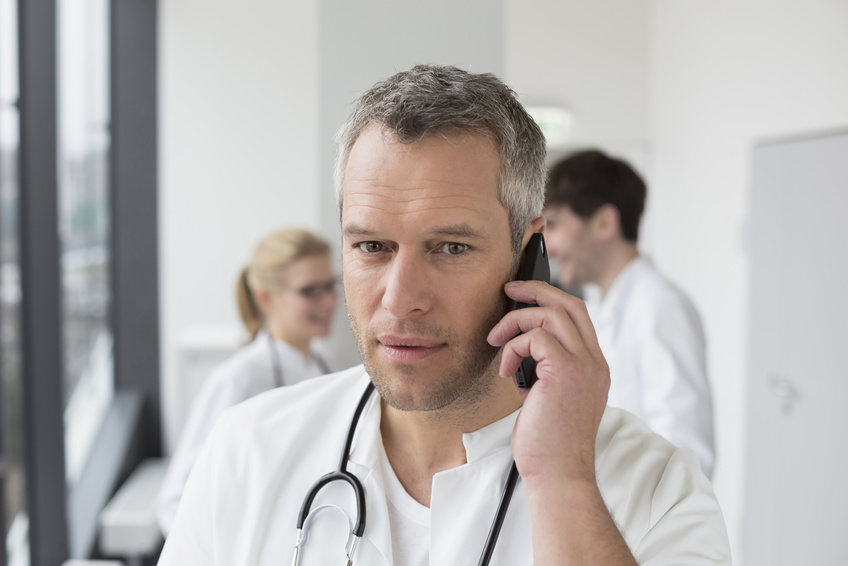 w25, m29, m44,  Portrait of a Doctor talking on the smartphone, in the background doctor colleagues, Saxony, Germany